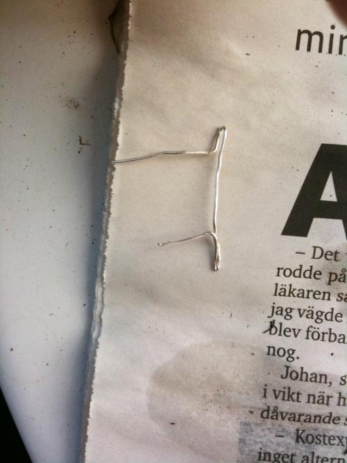 En bit ståltråd vikt som ett T ska hålla nätet på plats.